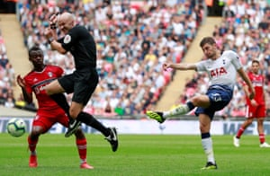 Referee Anthony Taylor attempts to get out of the way as Tottenham's Ben Davies shoots at goal.