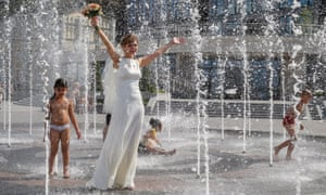 A bride cools off in Kiev, Ukraine, where temperatures reached over 36C.