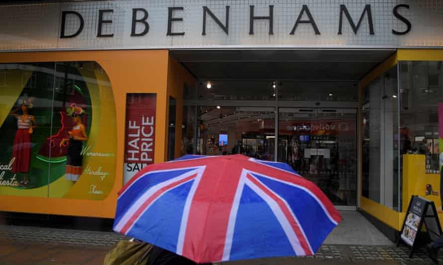 A shopper walks past a Debenhams store in central London clutching a union flag umbrella