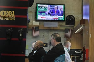 Traders work as U.S. President Trump is seen on monitor on the floor of the New York Stock Exchange (NYSE) in New York