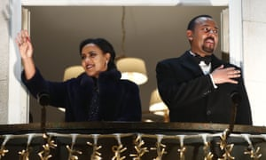 Abiy Ahmed and his wife Zinash Tayachew wave from the balcony of the Grand Hotel in Oslo on 10 December during a torch parade in honour of his Nobel peace prize.