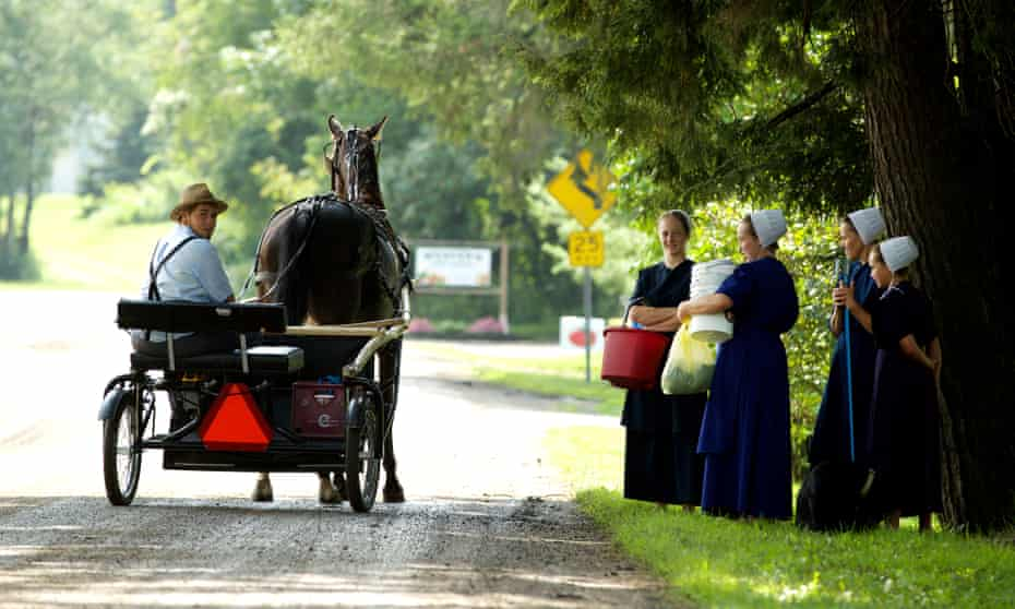 A horse-drawn cart in Morris passes women wearing traditional white bonnets