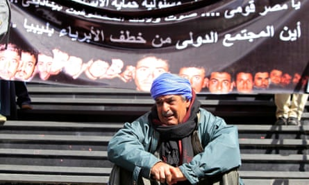 A family member the kidnapped men sits crying in front of a banner with pictures of the workers.