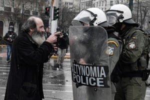 A priest argues with riot police in Athens