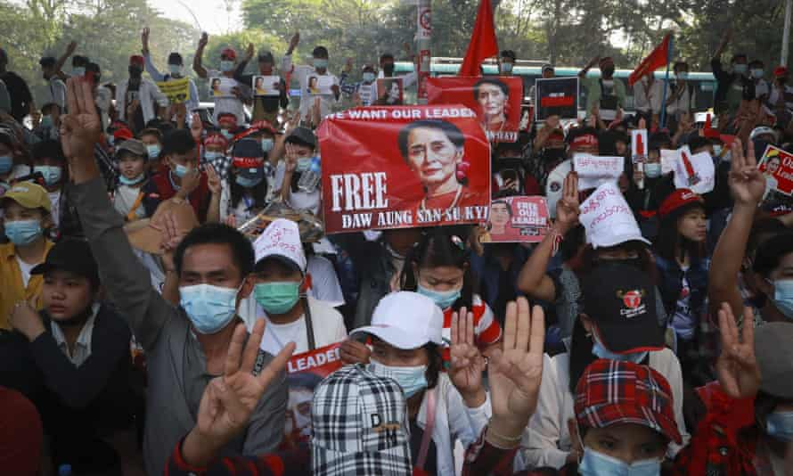 Protesters give a three-fingered salute of resistance during an anti-coup protest outside the Hledan Centre in Yangon.
