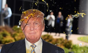 An egg is thrown at a cardboard cutout of  Donald Trump