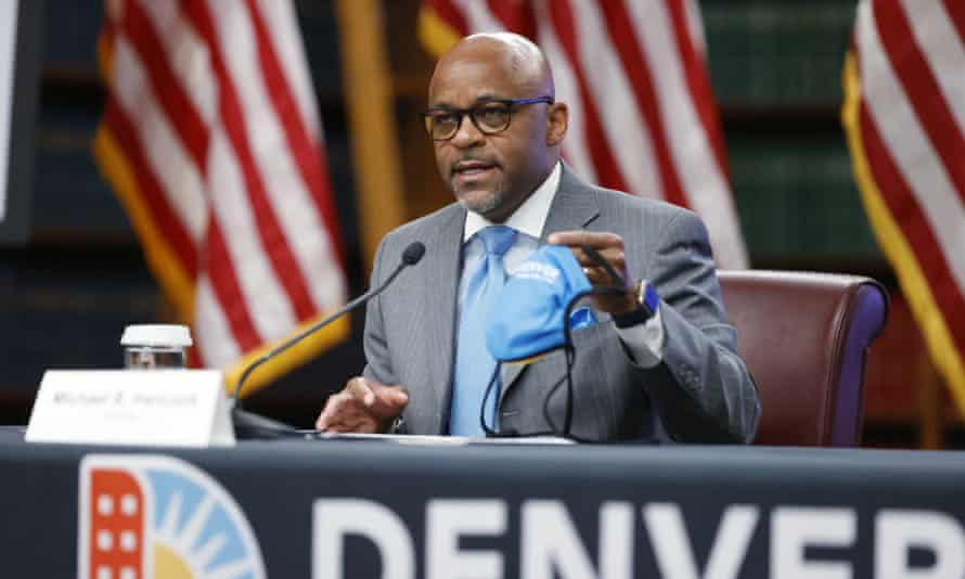 Denver's mayor, Michael Hancock, holds up a face mask during a news conference in Colorado on 5 May.