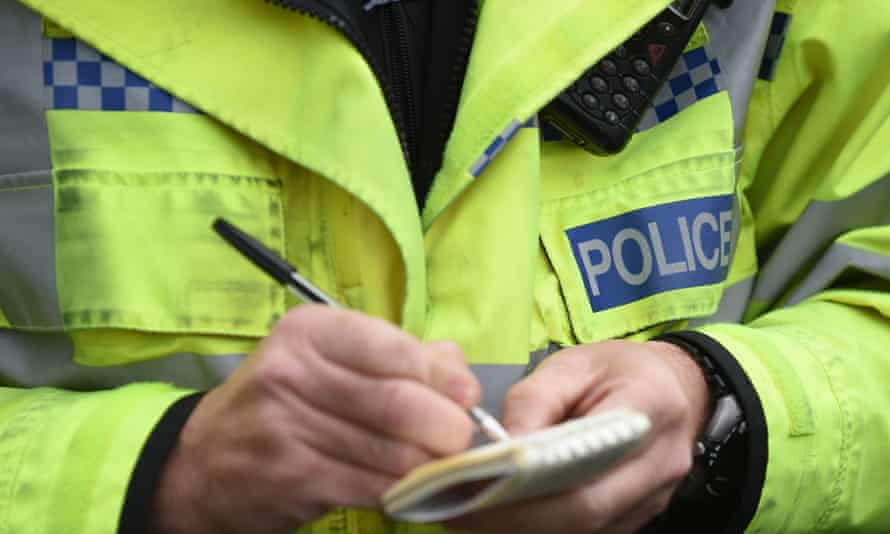 A police officer writes on a notepad