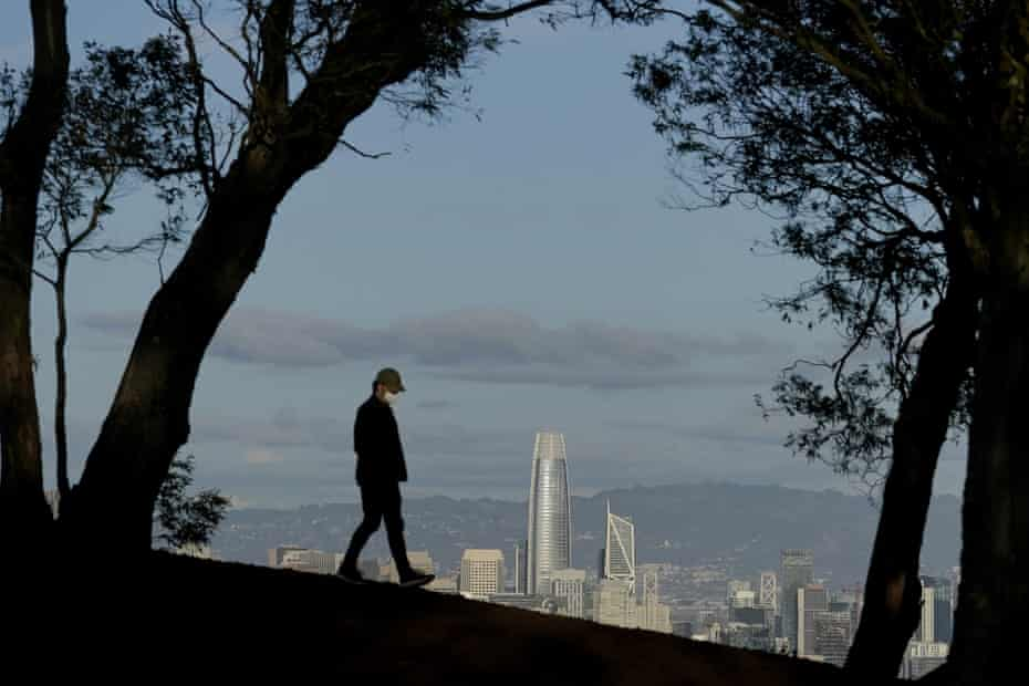 A person wearing a face mask walks atop Tank Hill in front of the San Francisco skyline in December.