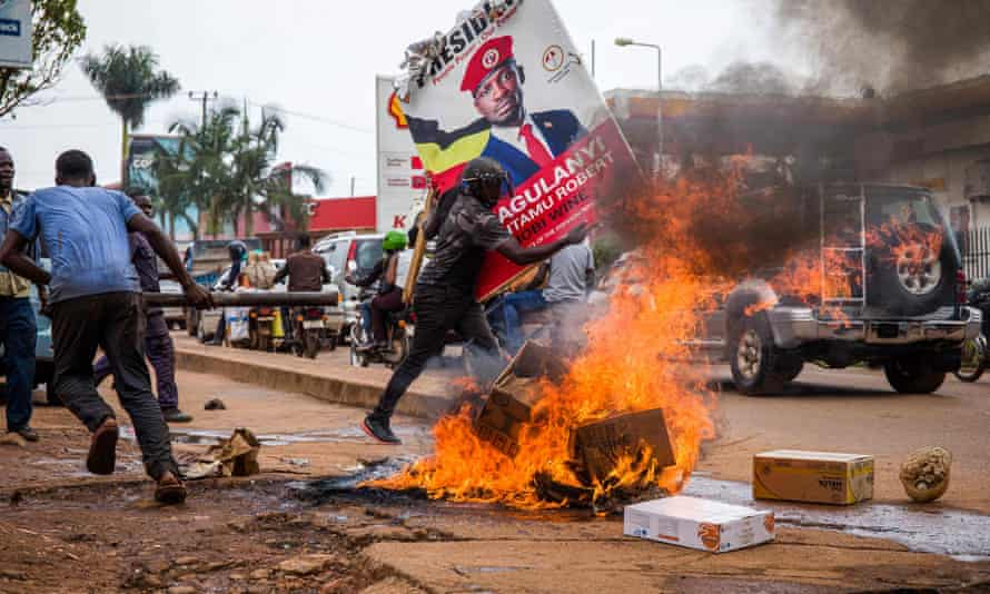 A supporter of Bobi Wine carries his poster as they protest against his arrest.
