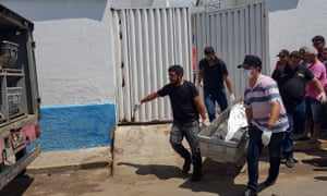 Forensic experts carry a dead body to be transported to the morgue after an attempted bank robbery in Milagres, Ceará state.