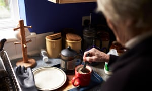 Older woman makes a pot of coffee in a kitchen.