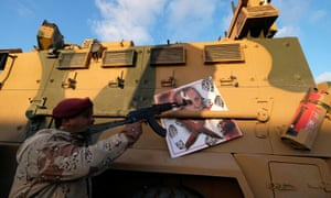A militiaman, under Khalifa Haftar, with a Turkish military armoured vehicle, which was confiscated during clashes in Benghazi, Libya, in January.