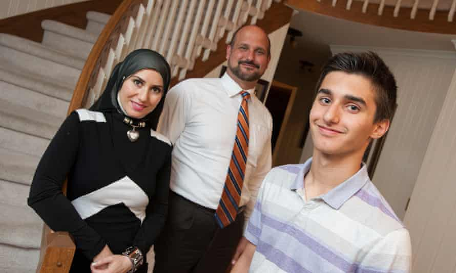 Hussein Murray, 15, poses for a photo with his mother Nisreen Murray and father Moheeb Murray on Wednesday in their Rochester Hills, Michigan home.