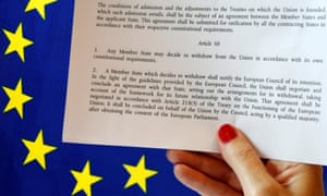 A hard copy of the Article 50 treaty clause held up against an EU flag