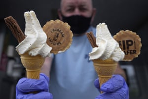 An ice cream vendor and climate activist holds out cones with a message at Swanpool beach in Falmouth