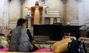 An Iraqi Christian woman fleeing the violence in Mosul sits inside the Sacred Heart of Jesus Chaldean Church in Telkaif in the province of Nineveh, July  2014