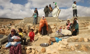 A Palestinian family sit next to the remains of their home