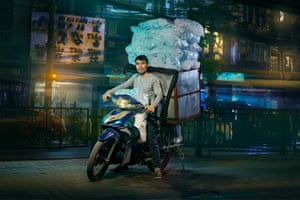 A delivery driver on a motorbike in Hanoi, Vietnam, carrying ice for bars and restaurants