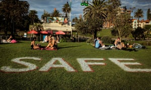People sitting on the grass in small groups, with the word 'SAFE' marked on the lawn