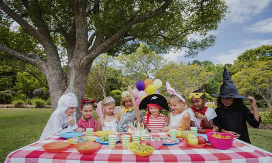Children at a fancy dress party outside under a tree