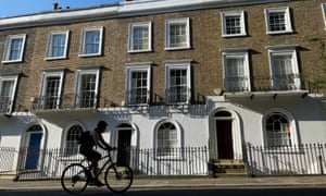 A cyclist rides past houses in Islington