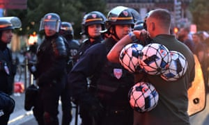 A French riot police officer talks to a football supporter in central Lille.