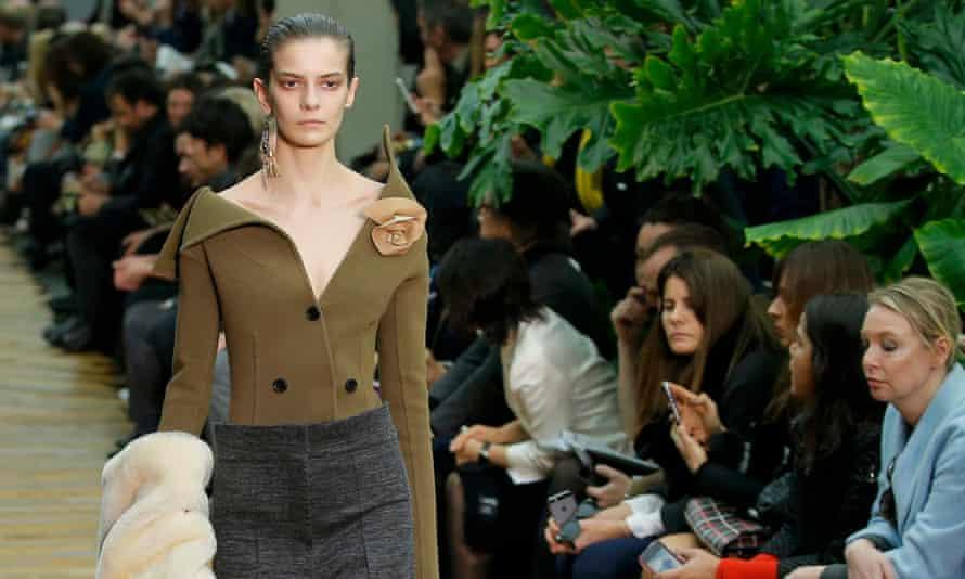 Model wears green jacket/top with unusual collar line
