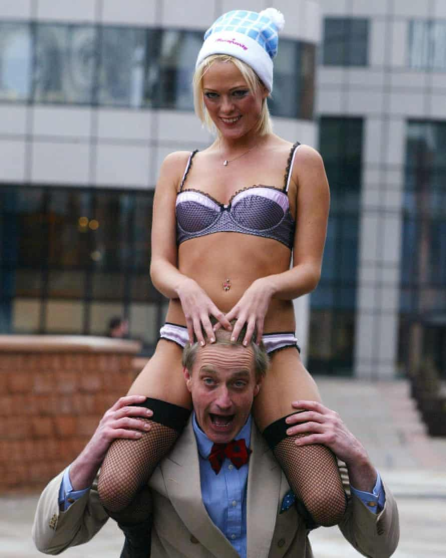Former Conservative MP Neil Hamilton poses with a model during the opening of the Erotica 2004 festival at Manchester's G-mex centre.