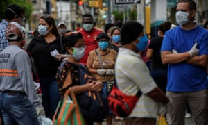 People line up outside of a pharmacy amid the outbreak of the coronavirus in Guayaquil.