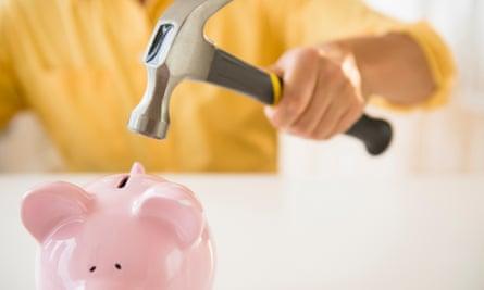 Man holding hammer over piggy bank