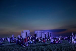 Revellers wait in the dark for the sun to rise on the shortest night of the year