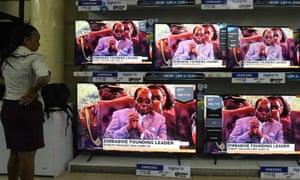 A Kenyan woman watches TV news announcing the death of Mugabe in Nairobi