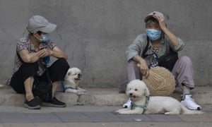 Two women wear masks to curb the spread of coronavirus chat as they sit on the sidewalk with their dogs in Beijing, China on Monday, 13 July 2020.
