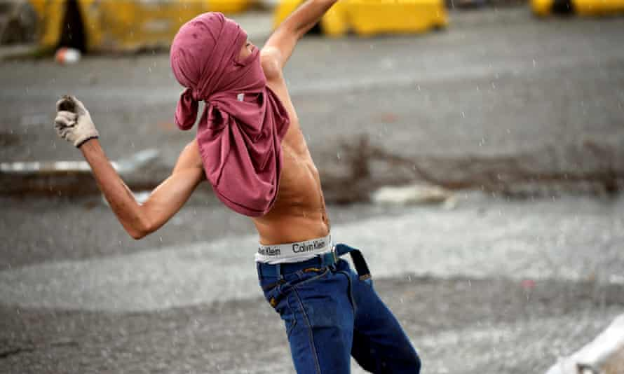A protester throws rocks during clashes with Venezuelan security forces near a military base, which was attacked by rebels on Sunday.