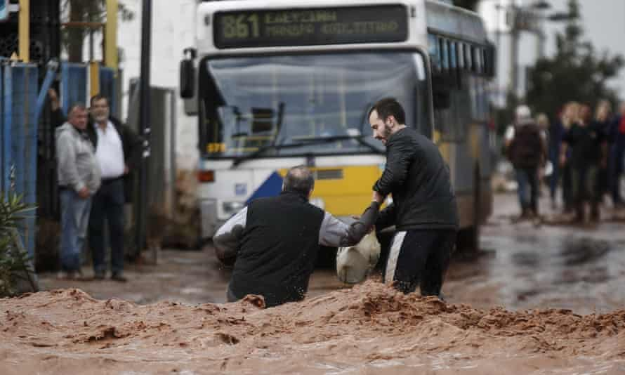 One man helps another on a flooded street in Mandra