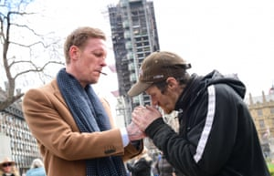 Westminster, UK. Laurence Fox, left, leader of the Reclaim party, lights a man's cigarette during the launch of his manifesto for the London mayoral election, in Parliament Square