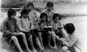 Peasants study Chairman Mao's quotations in the Little Red Book - the 'bible' of the Cultural Revolution during a break from rice planting, 1970, Guangxi, China.