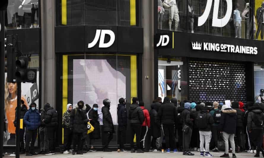 Gente esperando para comprar entrenadores cola fuera de JD Sports en Oxford Street en Londres