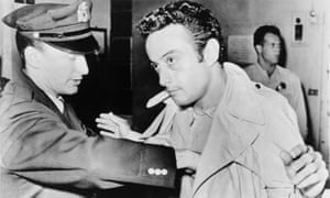 Lenny Bruce is searched at a police station after his 1961 arrest for using obscene language on stage.