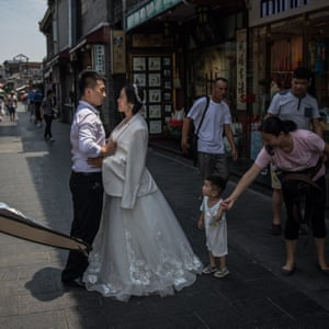A couple pose for their pre-wedding photos as people pass by in the Hutong neighbourhood in Beijing