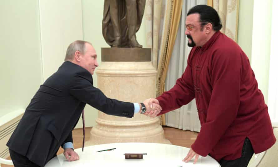 Putin shakes Seagal's hand after presenting him with a passport at the Kremlin.