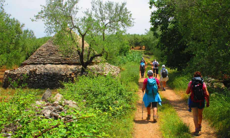 Walkers passing a trullo conical house