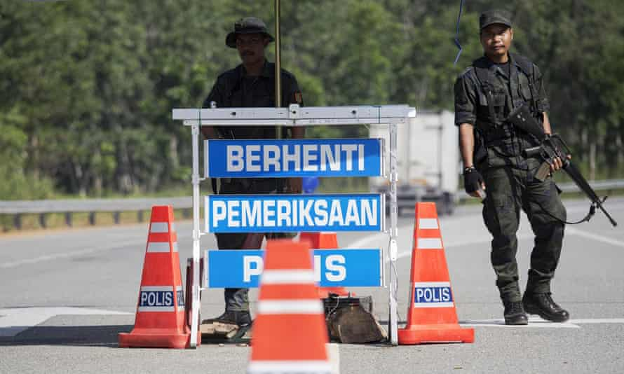 Members of Malaysia's General Operations Force control a checkpoint on the road near where an abandoned camp was discovered in the jungle close to the Thai border at Bukit Wang Burma in northern Malaysia.