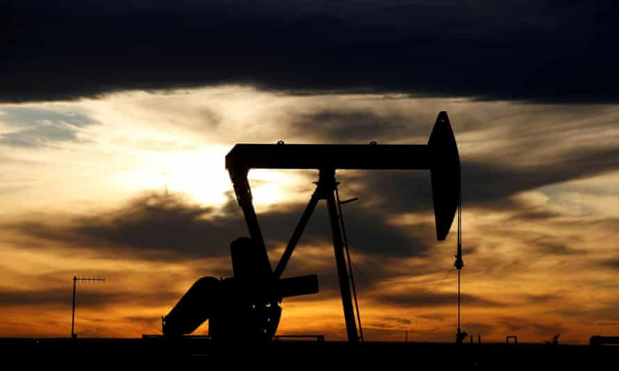 A crude oil pump jack on a drill pad silhouetted at dawn in the Permian Basin in Loving County, Texas.