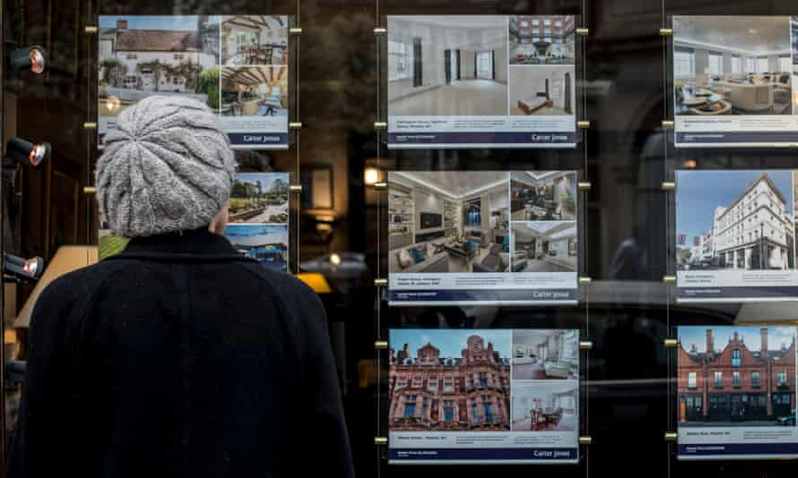 a woman looks at homes for sale through an estate agent's window