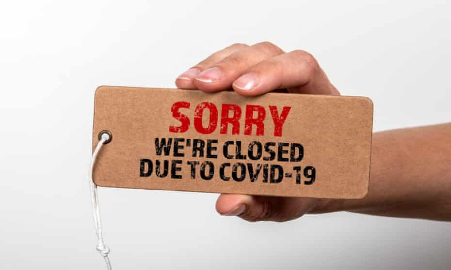 A hand holding up a sign saying 'Sorry, we're closed due to Covid-19'
