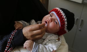 A health worker administers a polio vaccine on a child in Sana'a, Yemen.