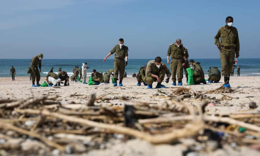 Israeli soldiers search for tar grains while cleaning Palmachim beach near the city of Rishon LeZion, Israel