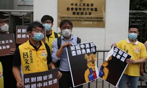 Local district councillors tear a poster depicting Winnie the Pooh tearing up the 1984 Sino-British Joint Declaration, during a protest against a newly proposed national security law outside the China Liaison Office in Hong Kong, China, 24 May 2020.